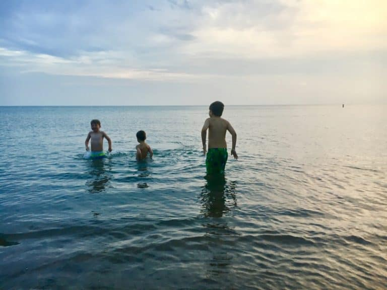 Boys swimming in Lake Michigan on family vacation road trip