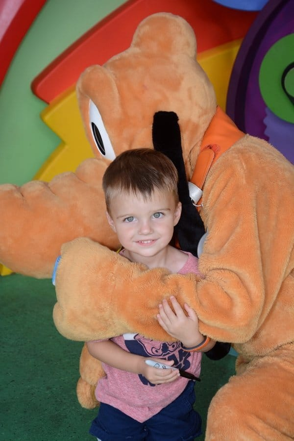 Young boy meeting Disney character on family vacation