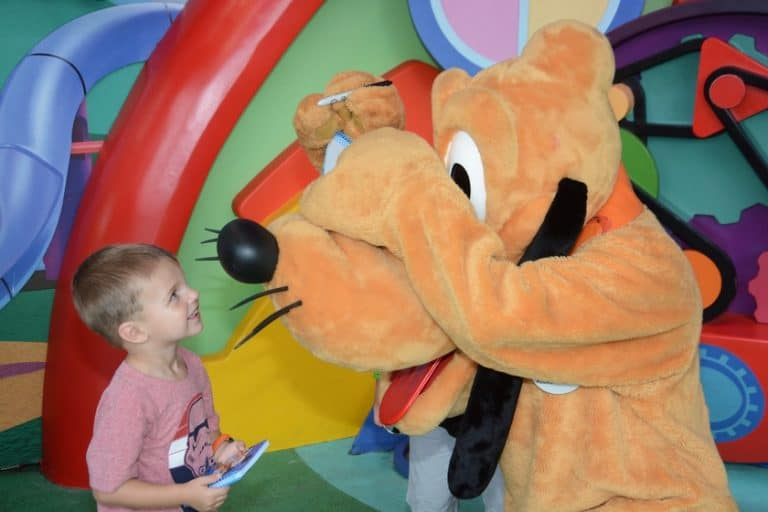 Pluto signing autograph with retractable Sharpie at Disney World