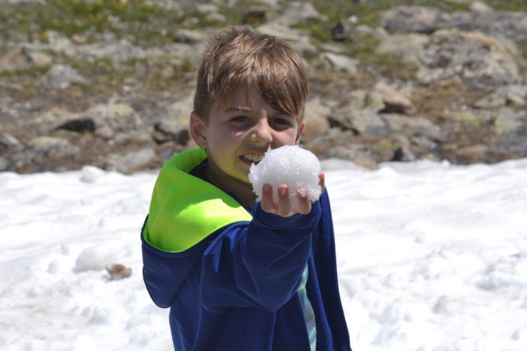 Young boy holding snow in Rocky Mountains on family vacation
