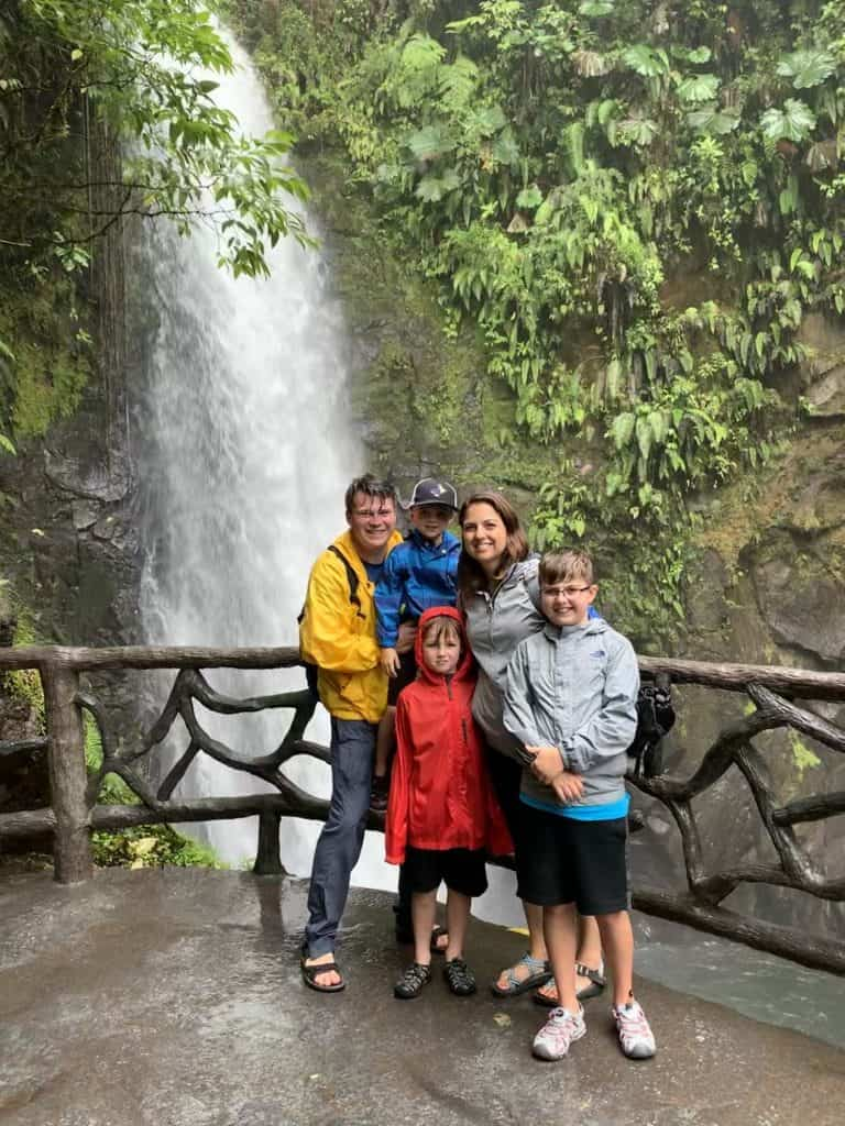 Family posing in front of waterfall at La Paz Waterfall Garden in Costa Rica