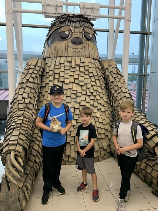 Boys posing with giant sloth in San Jose airport in Costa Rica