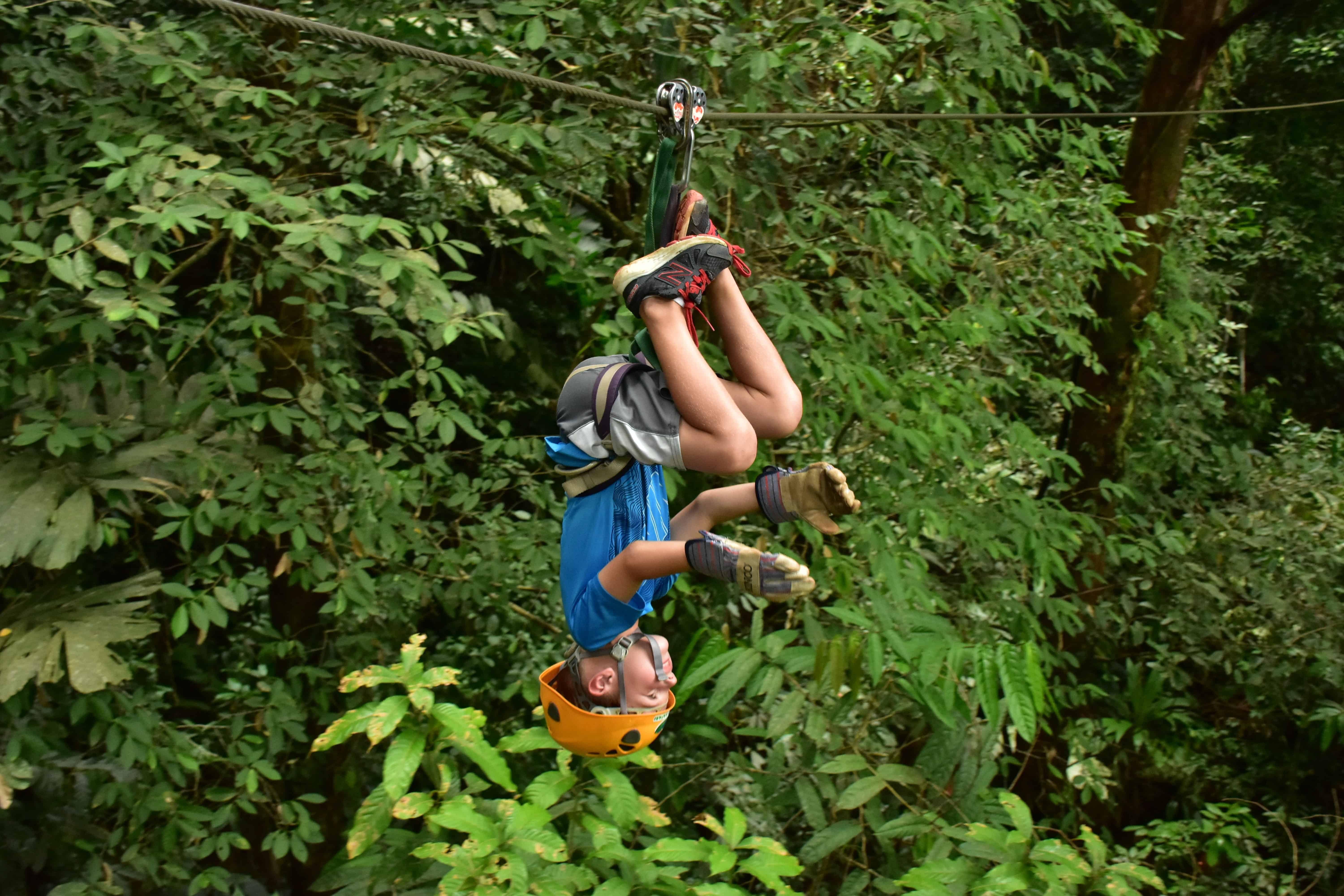 child zip lining upside down in costa rica