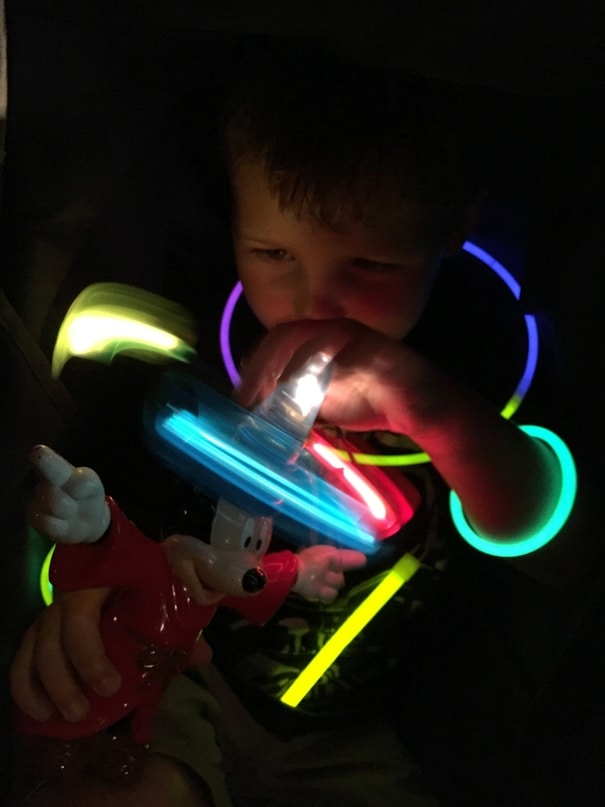 Child playing with glow sticks during Disney World Fireworks