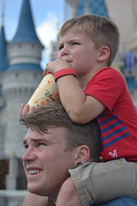 Father and son watching Disney parade