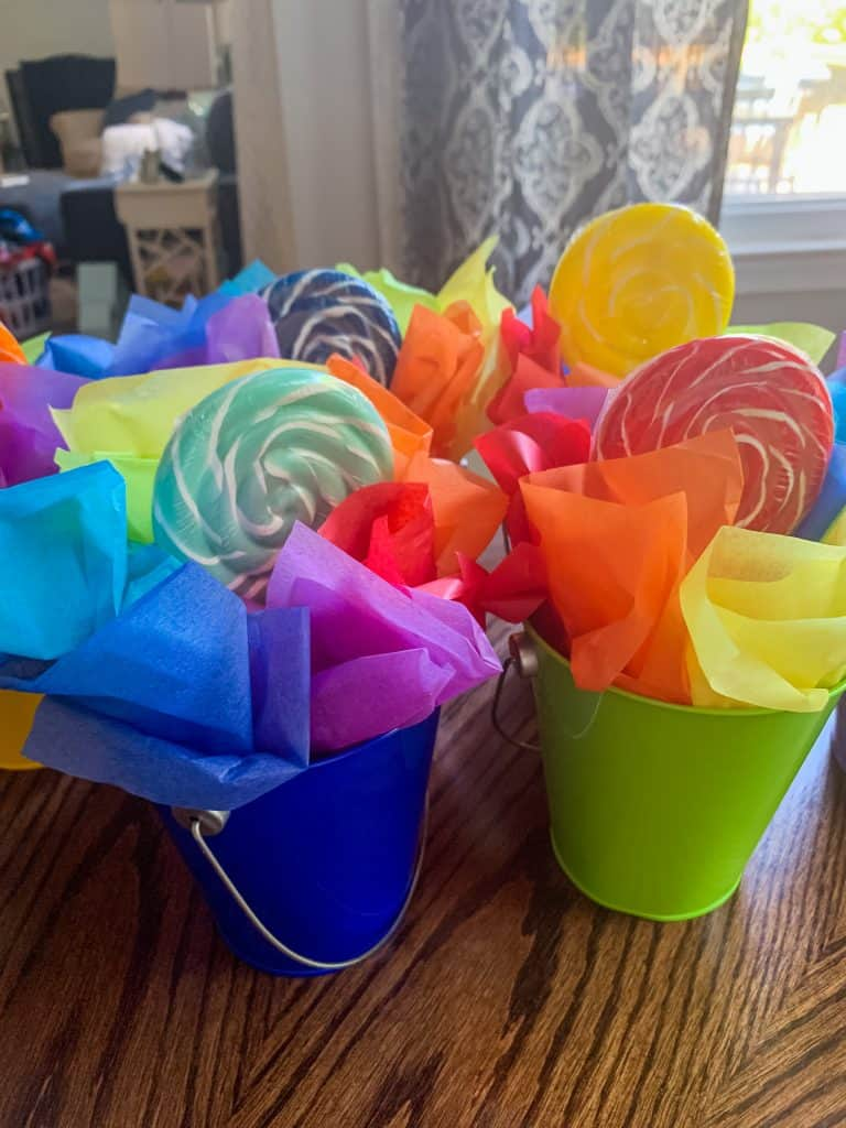 Lollipop candy themed centerpieces in metal buckets with tissue paper