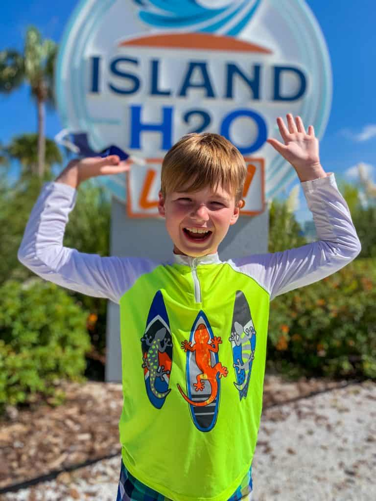 Boy in front of sign at entrance to Island H2O Live water park