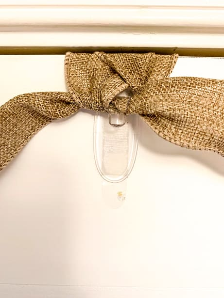 Burlap ribbon tied in knot to hang wreath on front door