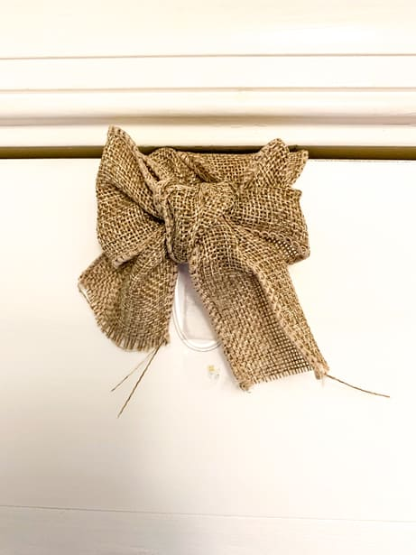 burlap ribbon bow holding a wreath
