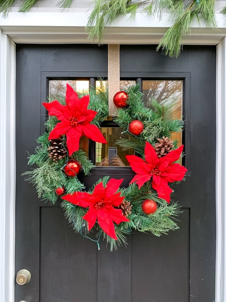 Christmas wreath hung on front door with ribbon