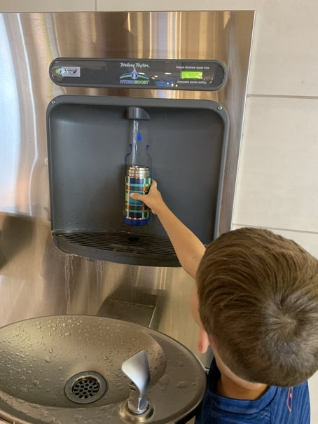 child filling water bottle at airport water fountain