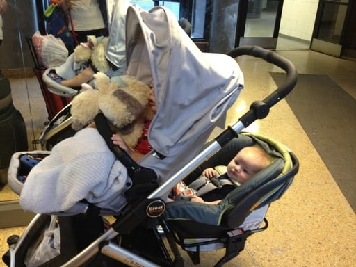 children in double stroller on the way to airport