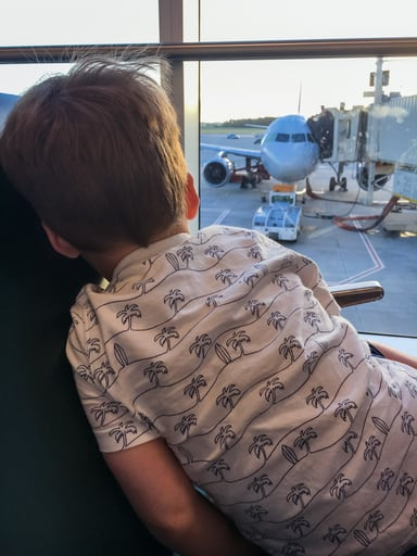 Child looking out airport window at airplane