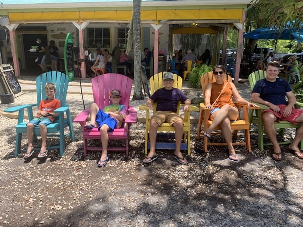 Family sitting in Adirondack chairs at Island Cow restaurant in Sanibel