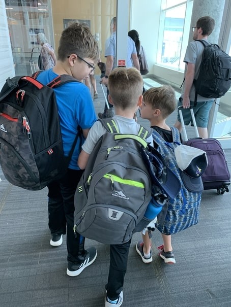 Young children carrying backpacks through airport security