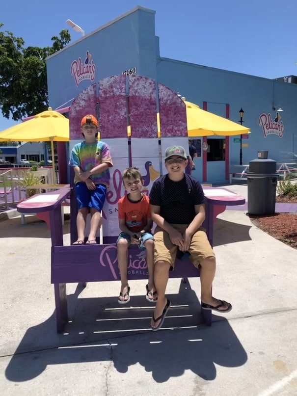 boys sitting on oversized Adirondack chair at Pelicans Snoballs in Fort Myers Beach