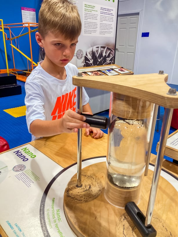 Boy playing with hands on activity at IMAG history and science center in Fort Myers, FL
