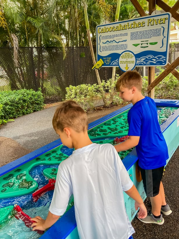 Boys playing in hands on water feature at IMAG history and science center in Fort Myers