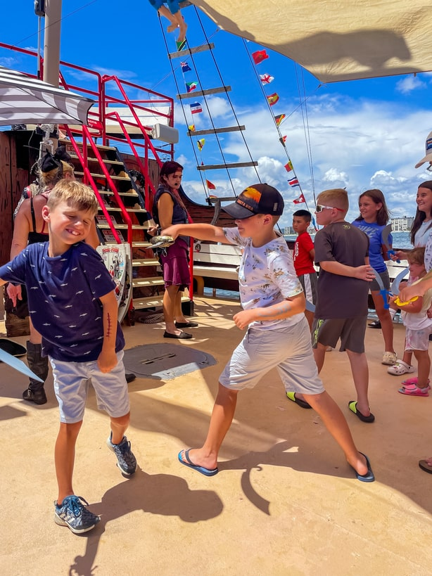 Kids having a sword fight aboard Salty Sam's Pirate Cruise in Fort Myers, FL