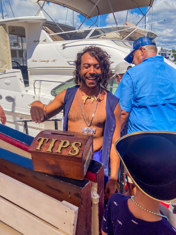 crew member accepting tips for salty sam's pirate cruise